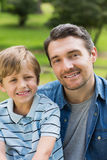 Close-up portrait of father and boy at park. Close-up portrait of a father and young boy sitting at the park stock photo