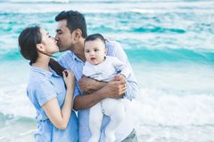 Father kissing mother while holding their cute son. Close up portrait of father kissing mother while holding their cute son at the beach royalty free stock images