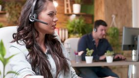 Close up portrait of female sales representative talking with a client through a headset. Busy but cozy office stock video