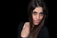 Close-up portrait of female subject affecting a serious sombre look. Woman with strongly facial features, looking at the camera, Black background Royalty Free Stock Images