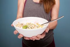 Fit woman with healthy breakfast. Close up portrait of fit mature woman hands holding a bowl of healthy breakfast Stock Images