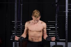 Close Up portrait of a fit young man lifting weights in gym on dark background. Close Up portrait of a fit young man lifting weights in gym on dark background Stock Photography