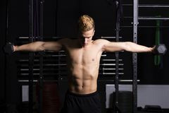 Close Up portrait of a fit young man lifting weights in gym on dark background. Close Up portrait of a fit young man lifting weights in gym on dark background Royalty Free Stock Photo