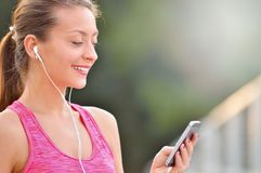 Close up portrait of fitness woman choosing music on her smartphone. Before or after jogging. Fitness girl training outdoor Royalty Free Stock Photo
