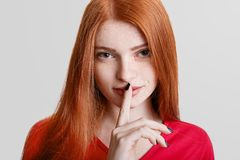 Close up portrait of freckled ginger young female holds index finger at lips, keeps silence, says:. `Shh`, demonstrates hush sign, isolated over white Stock Image