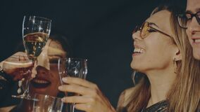 Close up portrait of friends at party celebrating birthday, drinking champagne or sparkling wine, pouring into glass