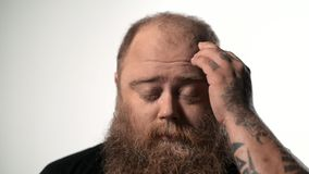 Despaired thick guy feels pain in head. Close up portrait of frustrated fat man suffering from headache. He is touching his temple with closed eyes and stock video footage