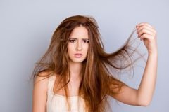 Close up portrait of frustrated young girl with messed hair on p. Ure  background, wearing white casual singlet, holding her hair Royalty Free Stock Photography