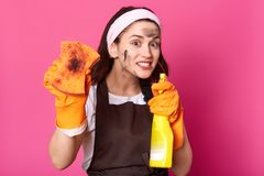Close up portrait of funny active brunette model points bottle of cleaning detergent at camera, showing dirty orange sponge, royalty free stock photo