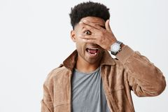 Close up portrait of funny beautiful black skinned man with afro hairdo in grey t-shirt under brown jacket looking Stock Photography