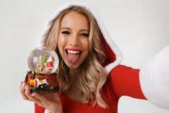 Close up portrait of a funny blonde woman. Dressed in red New Year costume standing isolated over white background, holding snowball, taking a selfie royalty free stock image