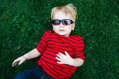 Close up portrait of funny cute adorable white Caucasian toddler child boy with blond hair in red pullover sunglasses Stock Photos