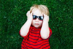 Close up portrait of funny cute adorable white Caucasian toddler child boy with blond hair in red pullover sunglasses Stock Photo