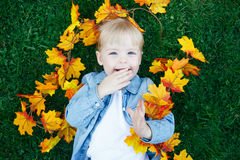 Close up portrait of funny cute smiling white Caucasian toddler child girl with blond hair lying on green grass with yellow leaves Royalty Free Stock Photo