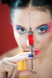 Girl looking at the syringe Stock Images