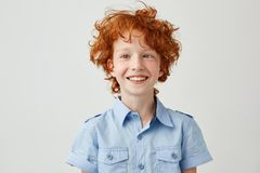 Close up portrait of funny little boy with orange hair and freckles mowing eyes, smiling and making silly faces for Royalty Free Stock Images