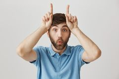 Close-up portrait of funny positive young guy with beard, making faces and holding index fingers over forehead, pointing Royalty Free Stock Photography