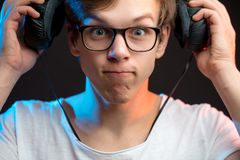 Close up portrait of funny singer taking off headphones. After rehearsalisolated black background Stock Image