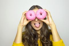 Close-up portrait of funny smiling girl with donuts isolated on gray background. Attractive young woman with long hair stock photography
