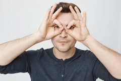 Close-up portrait of funny young guy making stupid face while showing glasses with hands and looking through it. Standing over gray background. I am watching Royalty Free Stock Image