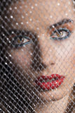 Close-up portrait of girl behind net Royalty Free Stock Photography