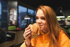 Close-up portrait of a girl holding a great tasty burger in her hand and laughing royalty free stock image