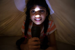 Close-up portrait of girl holding illuminated flashlight under blanket. On bed at home Royalty Free Stock Photo