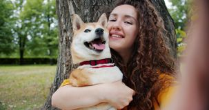 Close-up portrait of girl kissing dog in park taking selfie holding camera. Close-up portrait of curly-haired girl kissing shiba inu dog in park taking selfie stock video footage