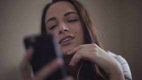 Close-up portrait of a girl listens to the music  on her smartphone through earphones. stock video footage