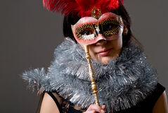 Close-up portrait of a girl in a mask with red feathers and tins Royalty Free Stock Photos