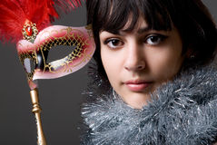 Close-up portrait of a girl in a mask with red feathers and tins Royalty Free Stock Images