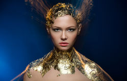Close-up portrait girl model in a stylish gold foil. Royalty Free Stock Photos