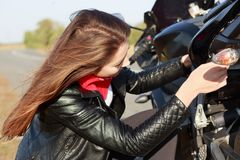 Close up portrait of girl motorist with long dark hair in jacket, trying to repair motorbike during trip, fixes some parts, has stock photography