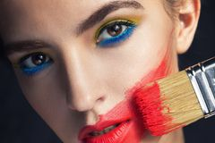 Close-up portrait of a girl with a paint brush royalty free stock photo