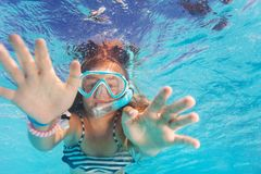 Cute little girl snorkeling in the pool. Close-up portrait of girl snorkeling in the pool and reaching camera Stock Image