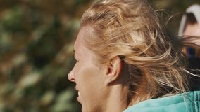 Close up portrait of a girl squints her eyes on summer windy day stock video footage