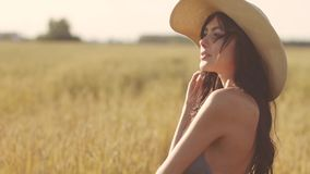 Close-up portrait of a girl in a straw hat in a wheat field stock video footage