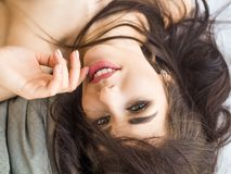 Close-up portrait of a girl with stunning dark hair, lying and looking at camera. Skin care concept.  royalty free stock photos