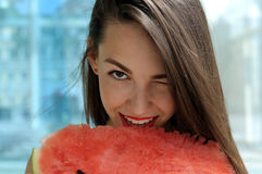 Close-up portrait of a girl who eats ripe watermelon. Smiling and winking against a blue background Stock Image