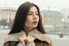 Close-up portrait of a girl who is walking around the city. The weather is cold and she is wearing a warm fur coat Stock Photo