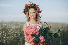 Close-up portrait of a girl with a wreath on her head and a basket of flowers royalty free stock image