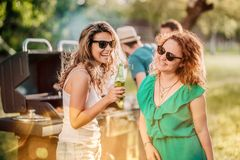 Close up portrait of girls drinking and laughing at backyard barbecue party royalty free stock image