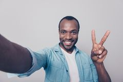 Close up portrait of glad excited cheerful handsome with beaming. Toothy smile foreigner demonstrating two sign and taking self portrait isolated on gray Stock Images
