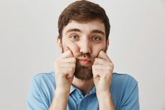 Close-up portrait of gloomy upset bearded male, squeezing cheeks with hands and looking at camera, being in bad mood. While standing over gray background. Guy royalty free stock photos