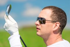 Portrait of a golfer looking at his golf club. Close-up portrait of a golfer looking at his golf club stock images
