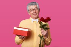 Close up portrait of good looking eldery man in spectacles, dressed in yellow shirt in one tone and white bowtie, carries red box stock photos