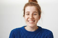 Close-up portrait of good-looking girl with freckles and natural red hair smiling nervously and chuckling, talking with. New company, feeling shy, standing over Royalty Free Stock Image