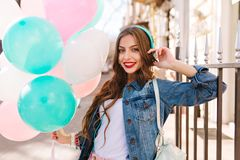 Close-up portrait of gorgeous curly girl in denim jacket posing with birthday balloons outside. Adorable young woman in