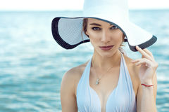 Close up portrait of gorgeous elegant glam lady wearing white bra, wide-brimmed hat and golden chain. With pendant at the seaside looking straight. Vogue Stock Image