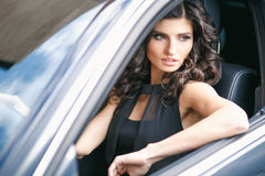 Close-up portrait of gorgeous young brunette woman driving an expensive car Royalty Free Stock Photography
